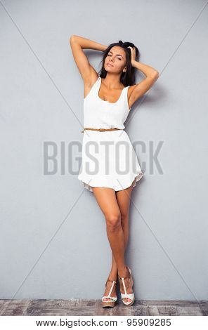 Full length portrait of a sexy cute female model in fashion white dress posing at studio and looking at camera