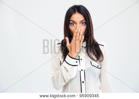 Young shocked woman covering her mouth with palm isolated on a white background. Looking at camera