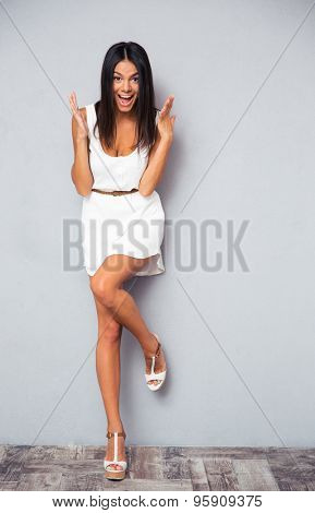 Full length portrait of a happy amazed woman standing on gray background