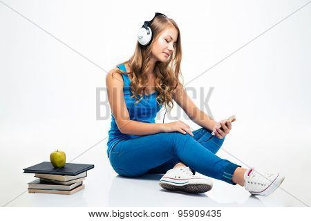 Beautiful young woman sitting on the floor with headphones and using smartphone isolated on a white background