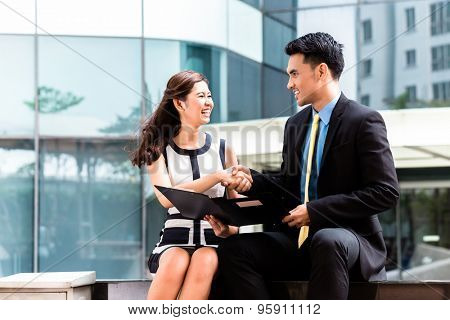 Asian business men and woman outside in front of tower building shaking hands