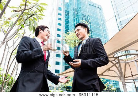 Asian business men having coffee break in front of tower building