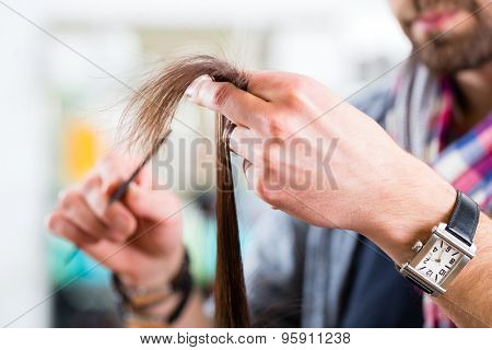 Male hairdresser cutting woman hair in hairdresser shop