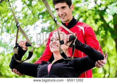 Sport woman with trainer at sling training