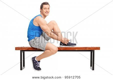 Young male athlete tying his shoelaces and looking at the camera seated on a wooden bench isolated on white background
