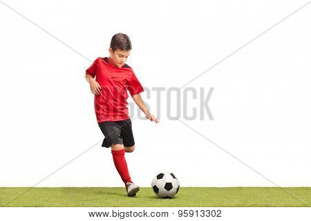 Little kid in red football jersey kicking a football on a grass surface isolated on white background