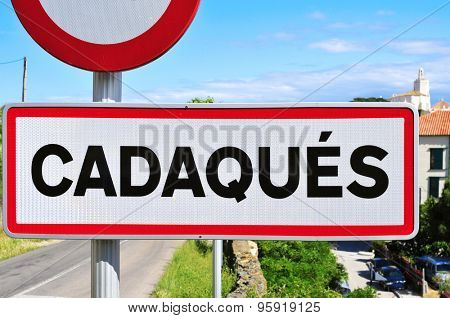 closeup of a road sign with the name Cadaques written in it at the entrance of Cadaques, in the Costa Brava, Spain