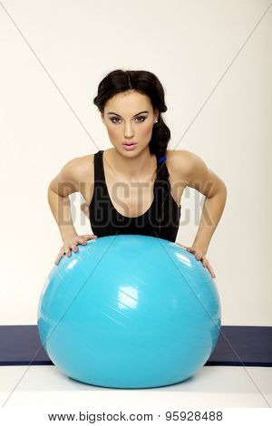 Portrait of a beautiful attractive young adult pretty brunette sporty woman in black dress with blue fitness ball isolated on white background