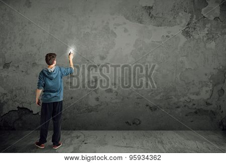 Young urban painter starting to draw graffiti on the wall