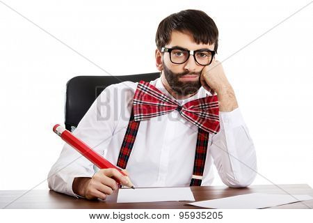 Worried old fashioned man sitting by a desk writing with big pencil.