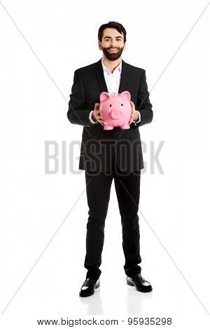 Happy handsome businessman holding a piggybank.