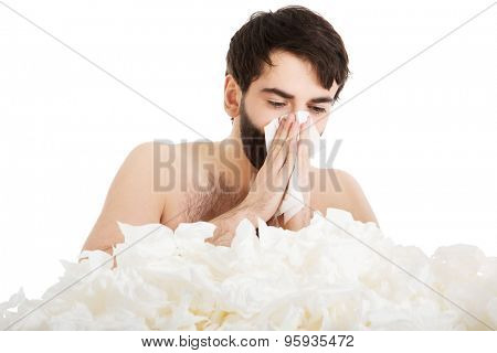 Sick man with a lot of tissues sneezing into handkerchief.