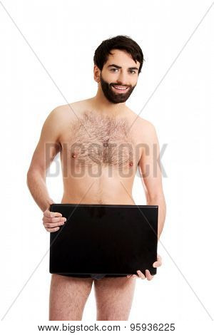 Young handsome shirtless man holding laptop.