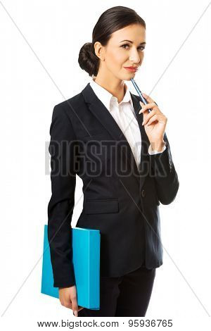 Beautiful pensive businesswoman holding a pen.