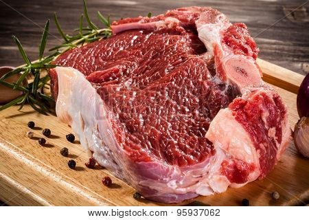 Raw beef on cutting board and vegetables
