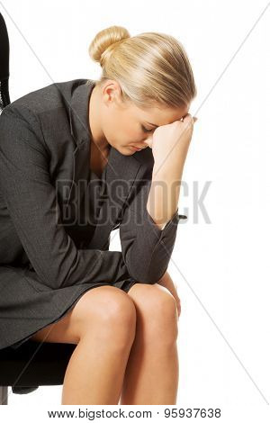 Depressed businesswoman sitting on armchair.