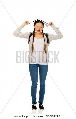 Frustrated teen girl with book over her head.