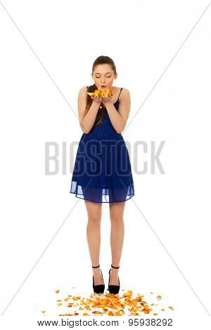 Beautiful teenage woman blowing rose petals.