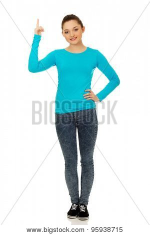 Happy beautiful young woman pointing up.