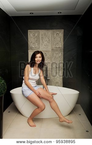 Natural beautiful woman sitting on bathtub in bathroom.