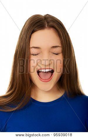 Angry teenage woman screaming loud.