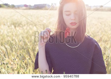 beautiful sexy cute girl with big lips and red lipstick in a black jacket with a flower poppy standi