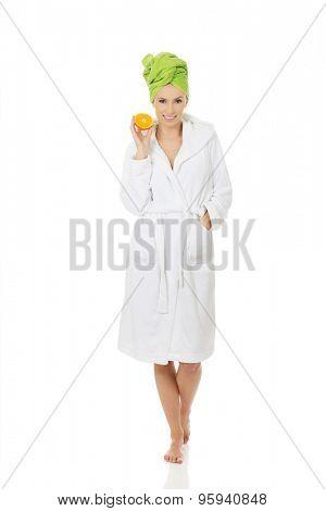 Beautiful spa woman in bathrobe holding orange.
