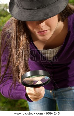Young Woman With Magnifier Glass And Hat Looking For Something On Outdoors Background