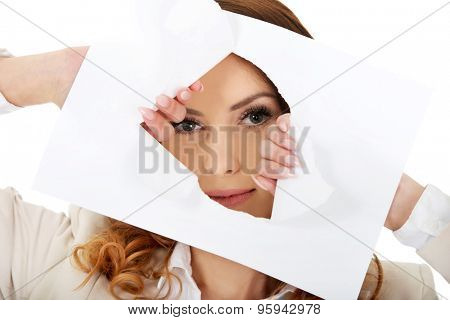 Businesswoman looking through tear paper sheet.