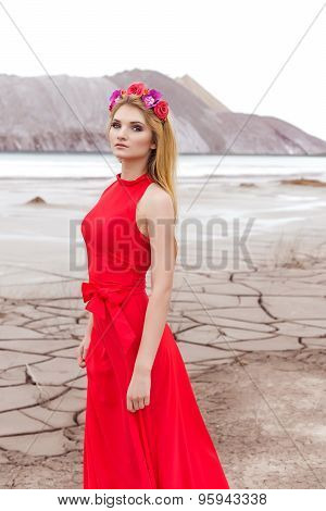 beautiful sexy cute girl with long blond hair in a long red evening dress with a wreath of roses