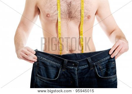 Man in dieting concept with oversized jeans.