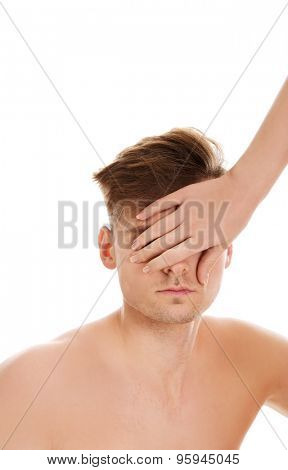Woman's hand covering shirtless man's eyes.