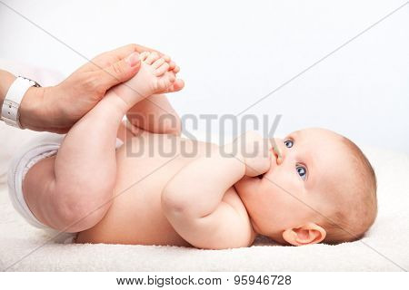 Close-up shot of three month baby girl receiving leg massage from a female massage therapist