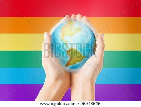 people, population and gay pride concept - close up of human hands with earth globe showing american continent over rainbow flag stripes background