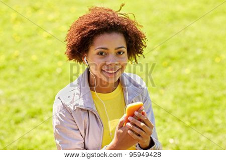 technology, lifestyle and people concept - happy african american young woman or teenage girl with smartphone and earphones listening to music in summer park