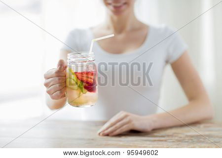 healthy eating, drinks, diet, detox and people concept - close up of happy woman holding glass with fruit water at home