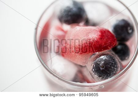healthy eating, drinks, diet and detox concept - close up of fruit water with strawberry, blackcurrant or blueberry and ice cubes in glass