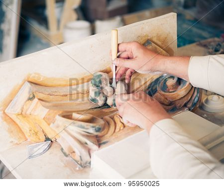 hands of restorer working with antique decor element