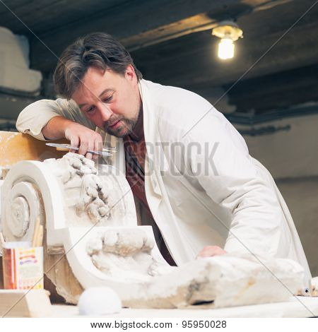 restorer working with gypsum model at workshop