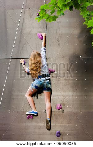 woman climbing artificial rock wall