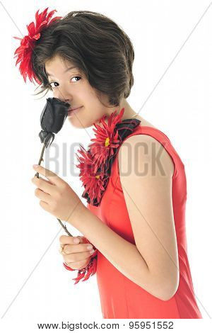 A beautiful young teen looking at the viewer as she sniffs a black rose while dressed for Cinco de Mayo in her red and black dress.  On a white background.