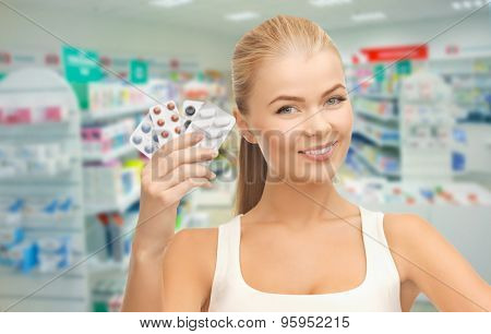 medicine, pharmacy, people, health care and pharmacology concept - happy young woman with variety of pills over drugstore background