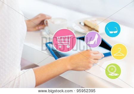 leisure, people, technology and online shopping concept - close up of young woman hands with tablet pc computer and internet icons having lunch at cafe