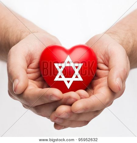 religion, christianity and charity concept - male hands holding red heart with star of david symbol