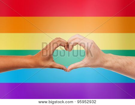 people, gay pride, gesture and homosexual concept - male and female multiracial hands showing heart shape symbol over rainbow flag stripes background