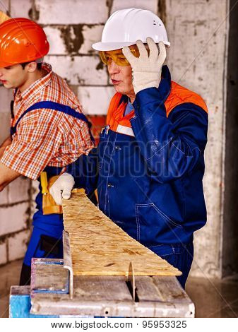 Group people  builder and old man with circular saw.