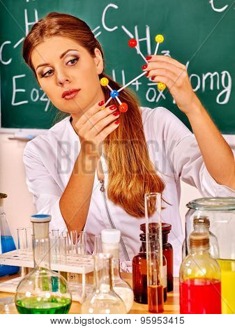 Chemistry young woman holding test-tube at classroom.
