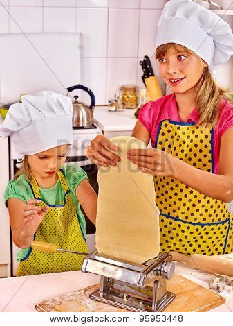 Older sister and younger child making homemade pasta at kitchen.