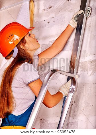 Happy working woman in builder uniform indoor.
