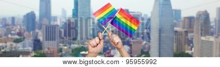 people, gay pride and homosexual concept - human hands holding rainbow flags over city background
